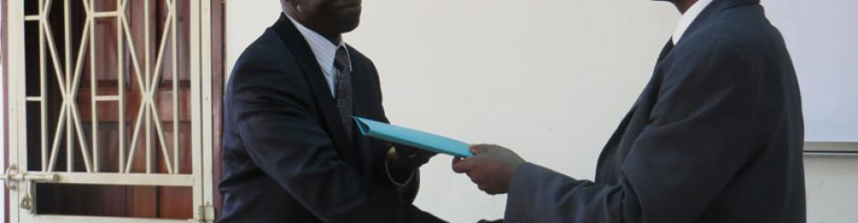 Prof Oswald Ndoleriire (R) hands over the principal mantle to Prof Edward Kirumira