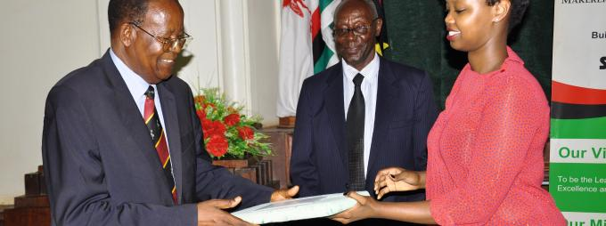 Dr Joshua Mugyenyi's daughter hands a present to Hon. Kamuntu.