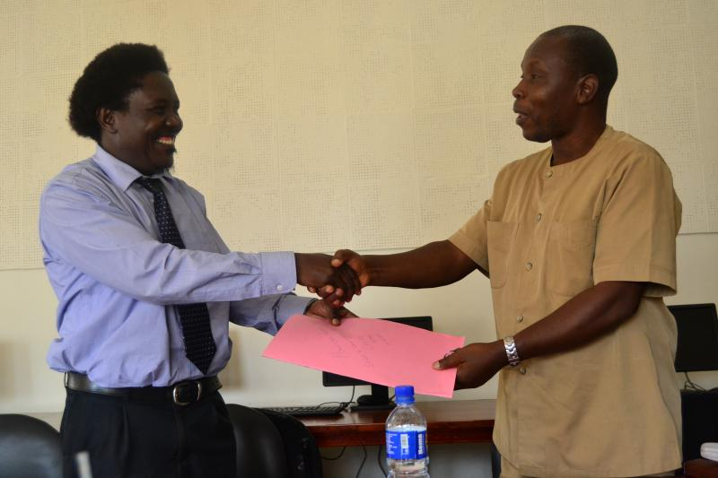 Dr Musana (R) gives the handover report to Dr Mangeni
