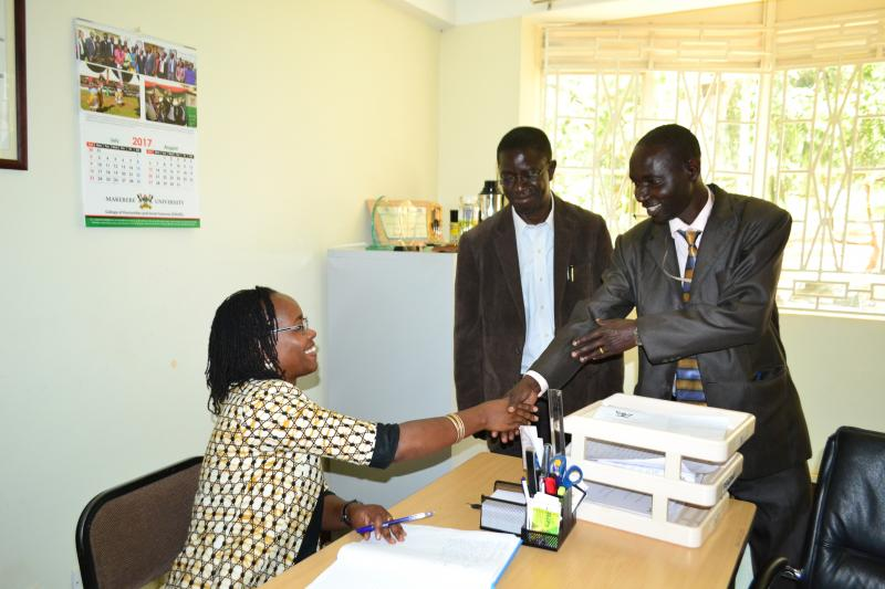 Dr Ssali being ushered into office by Mr Akonyet from Internal Audit and Prof. Kirumira
