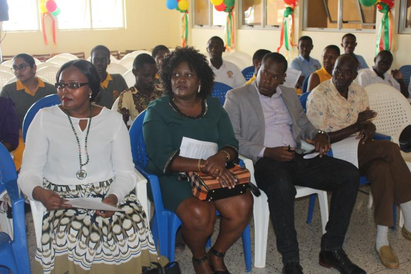 Guests and students of Makerere College School follow the proceedings