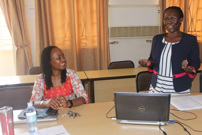 Dr Sylvia Nannyonga - Tamusuza (R) presents her research. Looking on is the Coordinator of the CHUSS Seminar Series, Dr Sarah Ssali