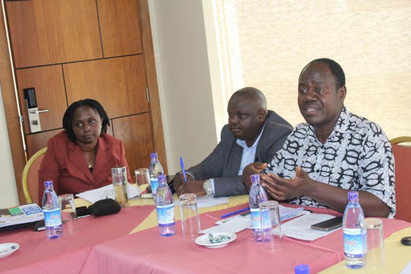 Dr Julius Kiiza (R) addresses participants