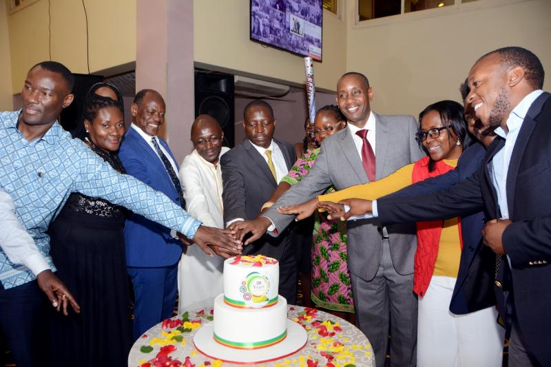 Some of the pioneer students cutting cake with Minister Bahati and Makerere University officials